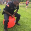 Officer Richardson hippity hops across Finn School's field